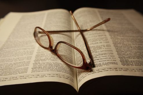 reading-glasses-atop-pages-of-open-dictionary-book-600x400.jpg